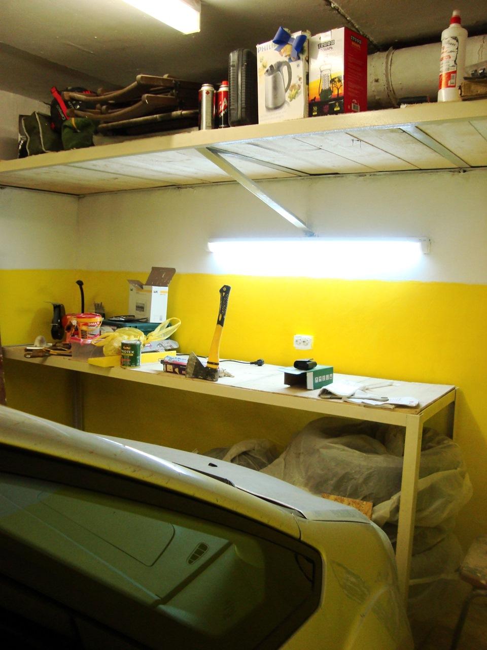 Дизайн гаража с желто-белыми крашеными стенами и полками под потолком по периметру